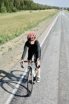 헬멧 스포츠 의류와 선글라스를 착용한 젊은 운동선수는 자연 속에서 자전거를 타고