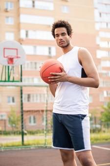 코트에 서있는 동안 농구를하기 위해 공을 들고 흰색 티셔츠와 스포츠 반바지에 젊은 선수