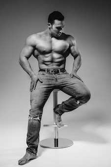 A young athlete in jeans poses sitting in the studio