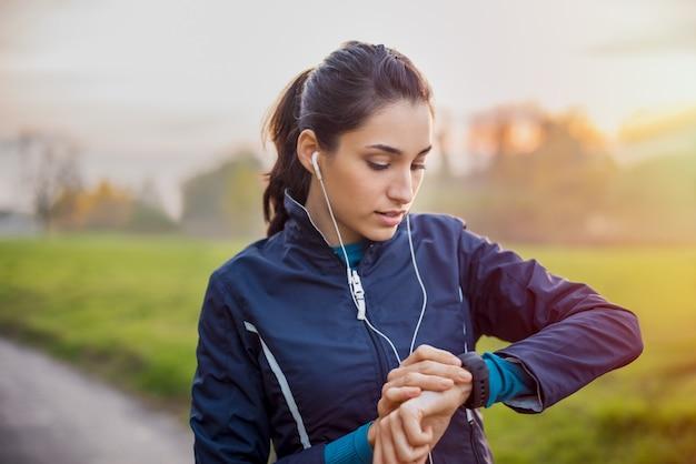 Молодой спортсмен слушает музыку во время тренировки в парке и регулирует умные часы