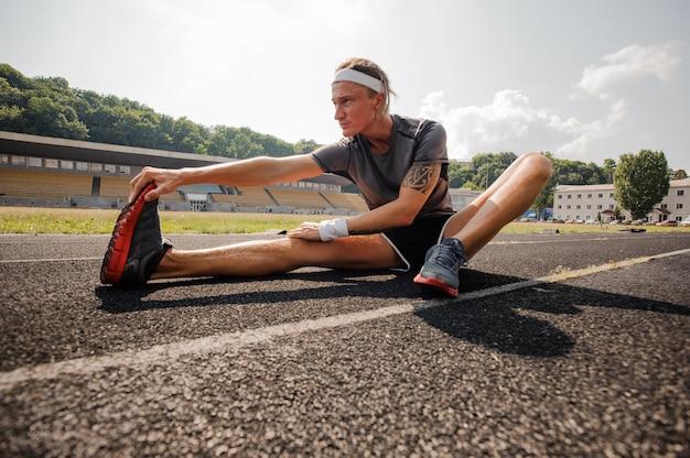 Молодой спортсмен делает растяжку в беговой дорожке