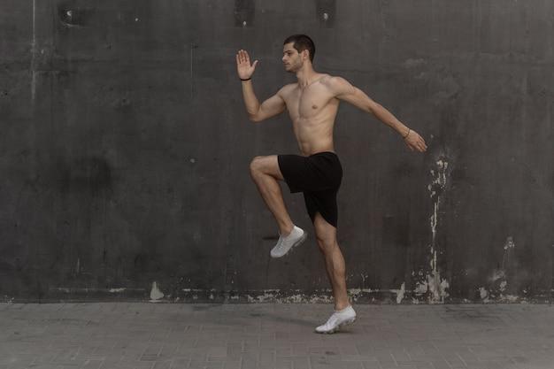 Uomo giovane atleta, torso nudo, in esecuzione contro un muro grigio