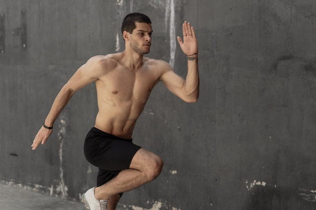 Young athlete man, naked torso, running against a gray wall