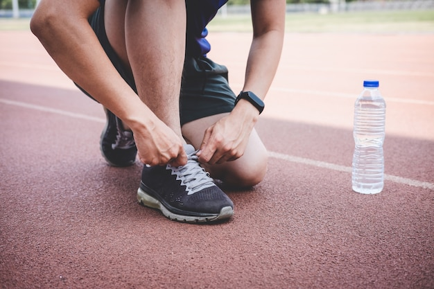 Young athlete man running on road track, exercise workout wellness and runner tying shoelaces