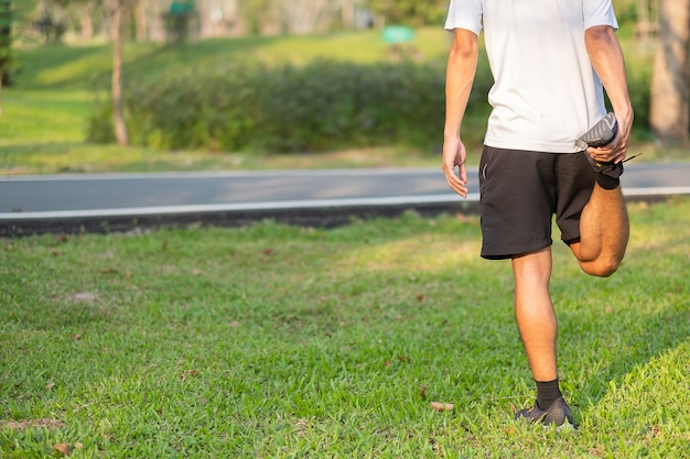 Молодой спортсмен человек растяжения в парке открытый.