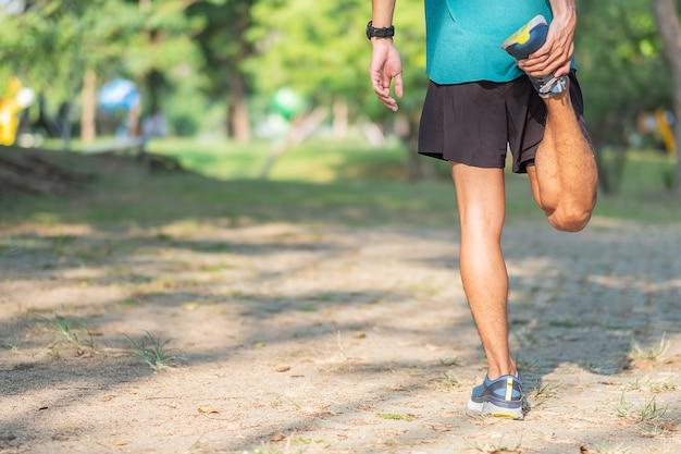 屋外の公園でストレッチ若い運動選手男。
