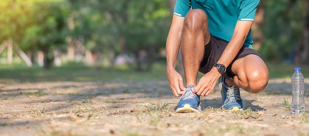 屋外の公園でランニングシューズを結ぶ若い運動選手男