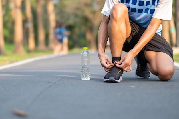 屋外の公園でランニングシューズを結ぶ若い運動選手男。