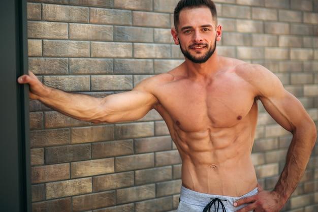 벽돌 벽 배경에 사진을 위해 몸통으로 포즈 젊은 선수. 보디 빌딩 용기구, 펌핑 된 근육을 가진 운동 선수, 가슴 및 팔 구조