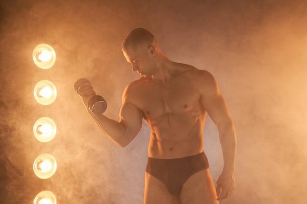 젊은 선수 펌핑 아령, 팔뚝 훈련 연습, 연기가 자욱한 조명 배경 건강한 라이프 스타일 개념입니다. 스포츠 및 피트니스 램프 광선 조명