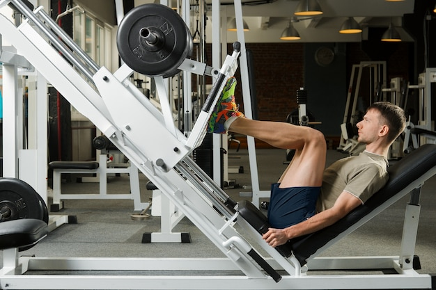 Young athlete pushing up barbell in gym
