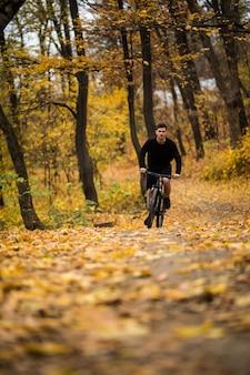 Молодой спортсмен ездить с велосипедом на осенний парк. подготовка к тренировке