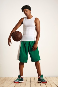 Young athlete in sleeveless white short, green basketball shorts and sneakers holding a vintage leather basketball to his side