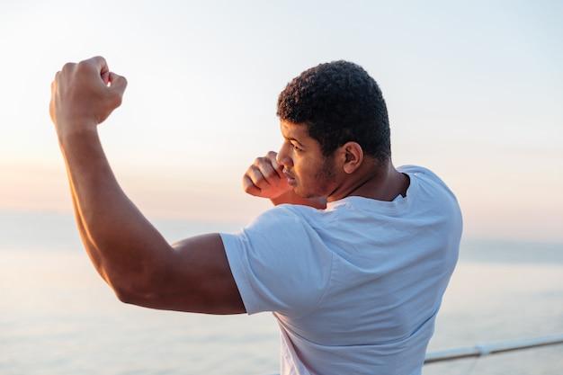 立って、屋外でシャドーボクシングを練習している若いアスリート