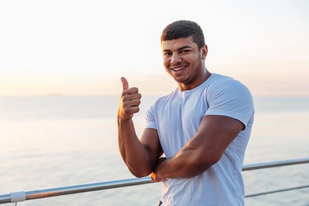 Молодой спортсмен стоит и показывает палец вверх на открытом воздухе