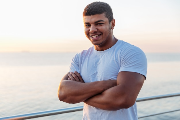 Young athlete standing with arms crossed on sunrise