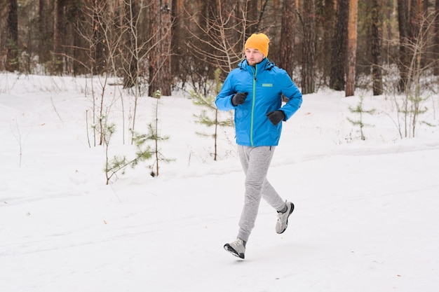 Young athlete in warm hat running along snowy path in winter forest while training alone