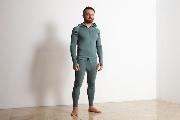 若いアスリートは、白い壁の前でポーズをとって、冬に緑のメリノウールベースレイヤーサーマルスイートを着用します