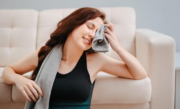 Молодой спортсмен вытирает пот полотенцем после интенсивных занятий фитнесом в домашних условиях.
