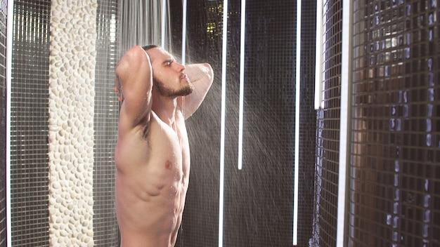 Молодой спортсмен с хорошим телосложением принимает душ. мужчина принимает душ