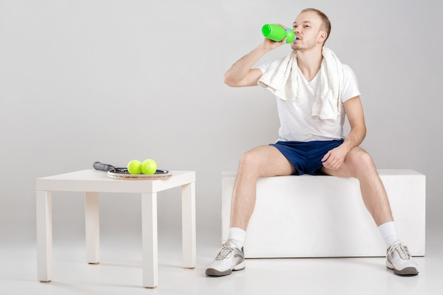 Young athlete with a towel drink water after a workout on a grey
