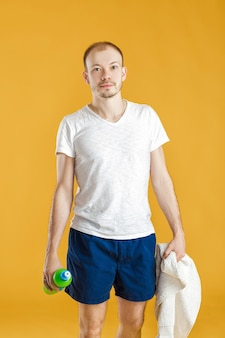 Young athlete with a towel drink water after a workout on a yellow