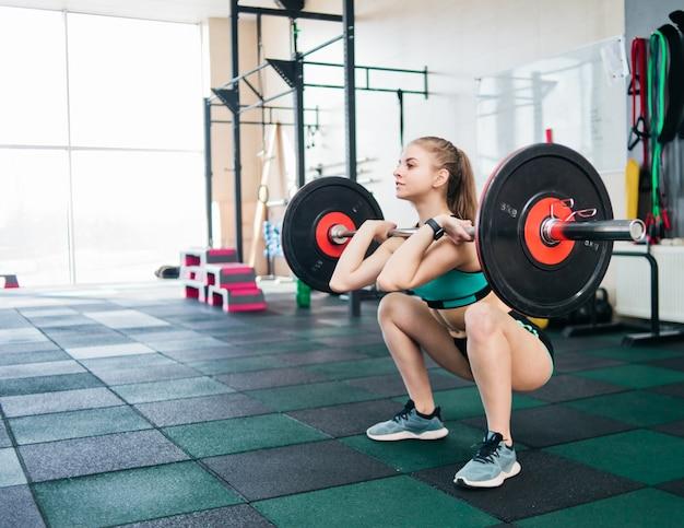 ジムで胸にバーベルをフロントスクワットを行うスポーツウエアで若い選手女性