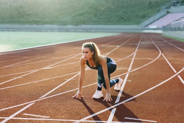 경주를 위해 열심히 준비하는 아침 가벼운 훈련에 트랙에서 빠르게 달리는 젊은 운동선수 여성