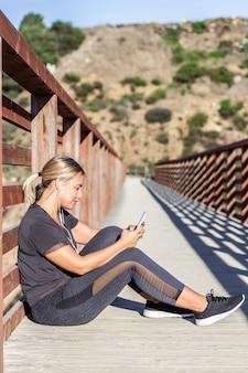 携帯電話とヘッドフォンで床に座っている若いアスリートの女性