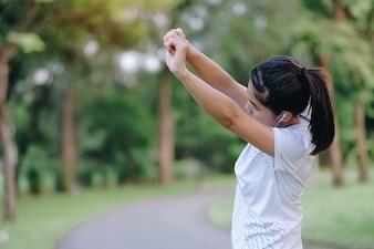 屋外の公園で若いアスリートの女性のストレッチ