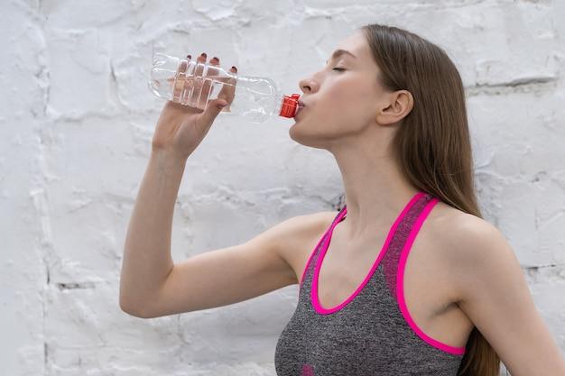 Молодая спортсменка делает перерыв питьевой водой из пластиковой бутылки.