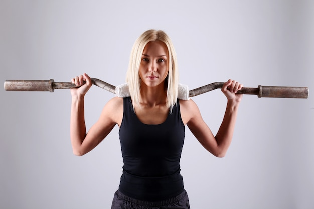 Young athlete woman with exercise bar