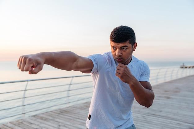 朝の桟橋で運動する若いアスリート