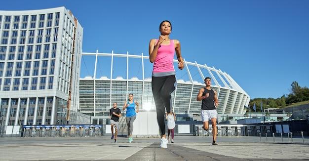 Молодые спортсмены соревнуются в беге на фоне стадиона