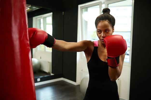 ボクシングジムでサンドバッグをパンチする完璧な体格を持つ若い運動アフリカの女性ボクサー。赤いボクシンググローブを身に着けている美しいスポーツウーマン。健康的でアクティブなライフスタイルのコンセプト