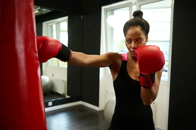 Young athletic african woman boxer with perfect physique punching a punching bag at boxing gym. beautiful sportswoman wearing red boxing gloves. healthy and active lifestyles concept