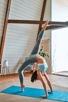 Молодая спортивная привлекательная женщина, практикующая йогу, делает упражнение «мост», одноногую позу колеса, тренировку, спортивную одежду, серые брюки, верх, полную длину в гостиной дома, вид сбоку.