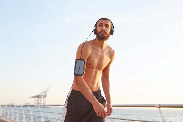 Giovane uomo barbuto atletico dopo lo sport estremo che cammina in riva al mare, distoglie lo sguardo e ascolta le canzoni preferite in cuffia,