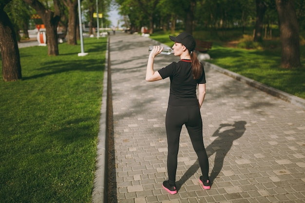 Young athletic beautiful brunette woman in black uniform and cap holding bottle, drinking water during training before running standing in city park outdoors