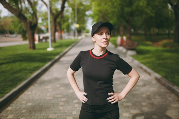 Young athletic beautiful brunette woman in black uniform and cap standing, doing sport exercises, warm-up before running, training on path in city park outdoors