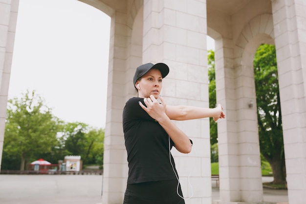 Young athletic beautiful brunette woman in black uniform, cap with earphones doing sport exercises, warm-up before running, listening to music in city park outdoors