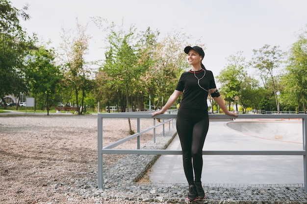 Young athletic beautiful brunette woman in black uniform and cap with earphones listening to music, standing before or after running, training in city park outdoors