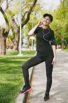 Young athletic beautiful brunette woman in black uniform and cap with earphones listening to music, standing before running, training on path in city park outdoors