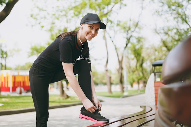 Young athletic beautiful brunette woman in black uniform and cap with earphones listening to music, tying shoelaces before running, training on bench in city park outdoors