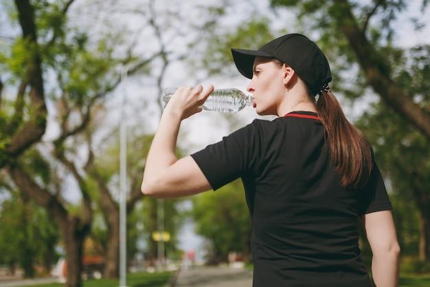 黒い制服とキャップ保持ボトル、屋外の都市公園に立って実行する前にトレーニング中に水を飲む若い運動の美しいブルネットの女性