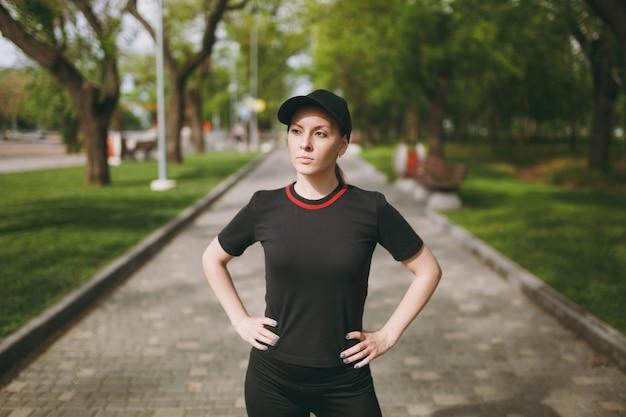 黒いユニフォームと帽子をかぶった若い運動の美しいブルネットの女性は、スポーツの練習をし、走る前にウォームアップし、屋外の都市公園の小道でトレーニングします