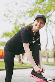 검은 제복을 입은 젊은 운동 아름 다운 갈색 머리 여자와 이어폰 음악을 듣고, 실행하기 전에 신발 끈을 묶고, 야외 도시 공원에서 벤치에서 훈련