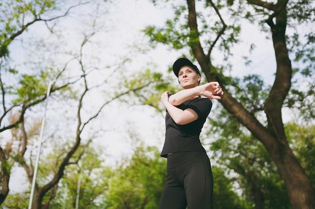 黒のユニフォームを着た若いアスリートの美しいブルネットの女性、スポーツストレッチ運動をしているキャップ、ランニングやトレーニングの前にウォームアップ、屋外の都市公園に立っている