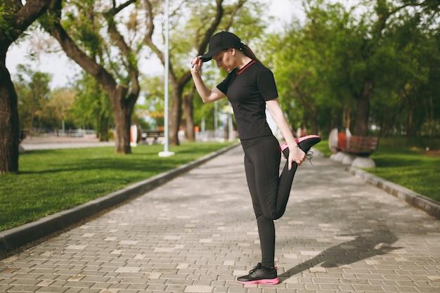 검은 제복을 입은 젊은 운동 아름다운 갈색 머리 여자, 스포츠 스트레칭 운동을하는 모자, 달리기 또는 훈련 전에 워밍업, 야외 도시 공원에 서