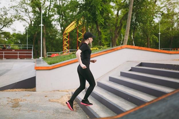 黒い制服を着た若いアスリートの美しいブルネットの女性、スポーツエクササイズ、トレーニング、ランニング、屋外の都市公園の階段に登るヘッドフォンでキャップ